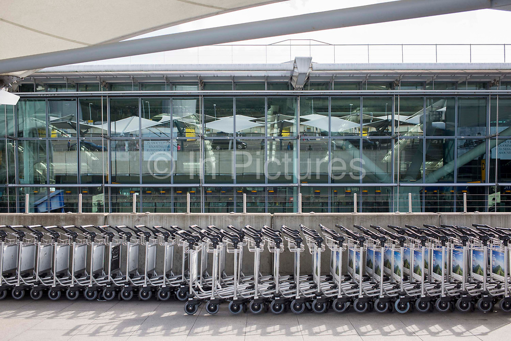Luggage trolleys outside departures of terminal 5 at Heathrow Airport, London, United Kingdom.