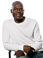 Portrait of a casual handsome afro American man smiling while sitting in studio on white isolated background