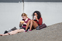 © London news pictures. 25/03/2017. Aberystwyth, UK.<br />  Two young women enjoying their lunch  on the beach on an afternoon of glorious sunshine and clear blue skies in Aberystwyth on the west wales coast, with temperatures expected to reach 18 or 19ºc by the afternoon. Sheltered from the cooling effects of an easterly wind, West Wales is expected to be the warmest pace in the UK today (Sat). Photo credit: Keith Morris/LNP