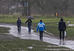 © Licensed to London News Pictures. 03/02/2021. London, UK. Walkers brave the rain and flooding on Wimbledon Common in South West London this morning. More rain and flooding has hit the South East today with flooding in Windsor and Oxfordshire as the Met Office issue weather warnings for rain and snow until Monday. Photo credit: Alex Lentati/LNP
