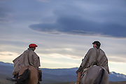 Gauchos on horseback overlooking the plains in twilight, Estancia Huechahue, Patagonia, Argentina, South America