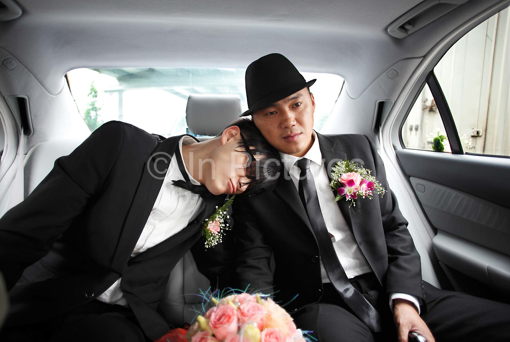 Coca Dai (right)  sits in his limousine with his best man on his way to pick up his bride in Shanghai, China on 23 May 2009. A hip street artist and a recent Catholic convert, Mr. Dai is one of many young Chinese embracing religion, perhaps to fill the lack of belief and ideology in an authoritarian communist China that embraces the most extreme form of capitalism in practice. The Chinese government and the Vatican have a long history of simmering mutual distrust and suspicion, as two parties compete for the control of the Chinese Catholic church, with some 15 million and growing number of faithfuls.  Overall Christians now number over 110 million in China, which makes it the third largest Christian nation in the world.