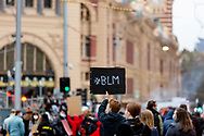 A Black Lives Matter placard is seen held above thousands of protesters during a Black Lives Mater rally on 06 June, 2020 in Melbourne, Australia. This event was organised to rally against aboriginal deaths in custody in Australia as well as in unity with protests across the United States following the killing of an unarmed black man George Floyd at the hands of a police officer in Minneapolis, Minnesota. (Photo by Dave Hewison/ Speed Media)