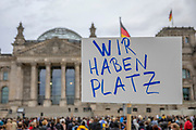 """A protester holds a banner reading """"We Have (enough) Space"""" as people take part in a demonstration in front the Reichstag  building, seat of the German lower house of Parliament, the Bundestag in Berlin, Germany, August 17, 2021. About 1000 people gathered in front of the  under the call """"Airlift now! Create safe escape routes from Afghanistan!"""", the spontaneous event was organized by Seebrücke and several other human-rights organizations."""