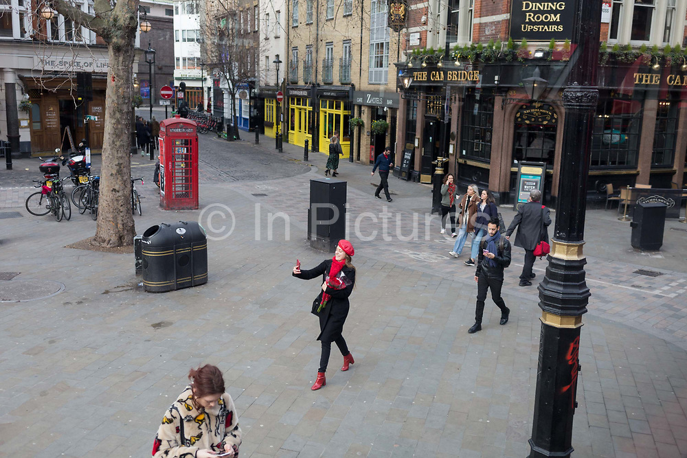 A young woman wearing a red theme of beret and scarf, walks down Charing Cross Road at Cambridge Circus in Soho, carrying some Valentines Day roses, and photographs herself with a beaming smile, on 14th February 2020, in London, England.