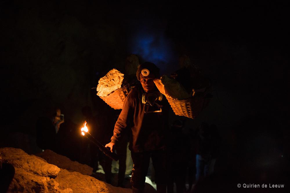Een mijnwerker draagt een mand met zwavelblokken uit de IJen-krater op Oost Java.<br /> <br /> De zwavel wordt door lokale mijnwerkers uit de Ijen-krater gewonnen. Met grote manden op de rug worden zware gele zwavelblokken uit de krater omhoog gedragen. Het werk wordt 's nachts tot' s ochtends vroeg uitgevoerd wanneer de temperatuur nog dragelijk is.