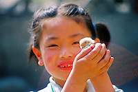 China, Beijing, 2008. An Easter surprise for this young girl along one of Beijing's quiet back streets. Chicks are a favorite pet for children in China..