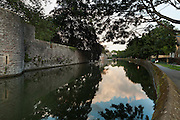 Reflection of a summer evening sky in the moat surrounding the Bishop's Palace in Wells, looking south along the western flank.