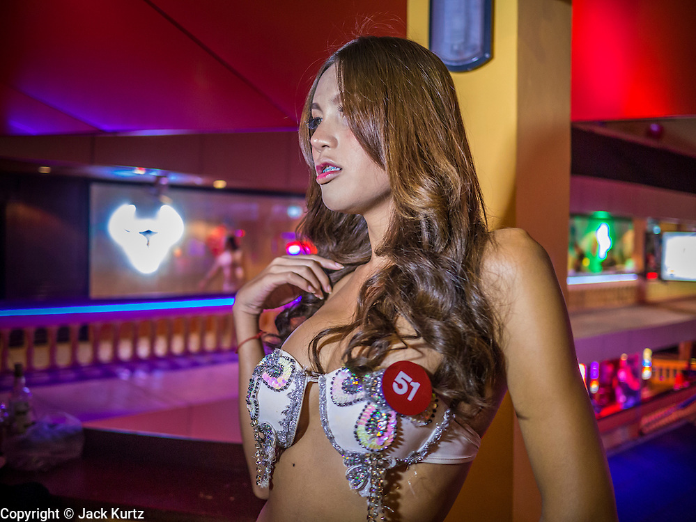 "05 JANUARY 2013 - BANGKOK, THAILAND: A sex worker poses for photos in the Nana Entertainment District in Bangkok. Prostitution in Thailand is technically illegal, although in practice it is tolerated and partly regulated. Prostitution is practiced openly throughout the country. The number of prostitutes is difficult to determine, estimates vary widely. Since the Vietnam War, Thailand has gained international notoriety among travelers from many countries as a sex tourism destination. One estimate published in 2003 placed the trade at US$ 4.3 billion per year or about three percent of the Thai economy. It has been suggested that at least 10% of tourist dollars may be spent on the sex trade. According to a 2001 report by the World Health Organisation: ""There are between 150,000 and 200,000 sex workers (in Thailand).""      PHOTO BY JACK KURTZ"