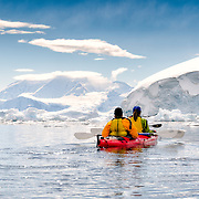 Kayakers in calm waters at Neko Harbour, Antarctica with scenic mountains and icebergs.