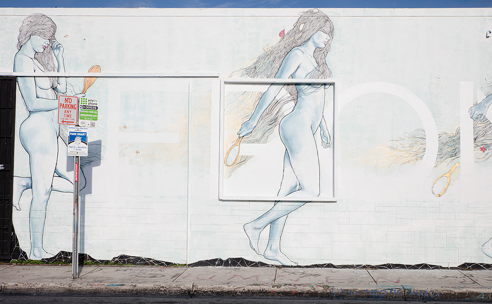 Two-story high, nude nymphs painted on the wall of a Wynwood warehouse
