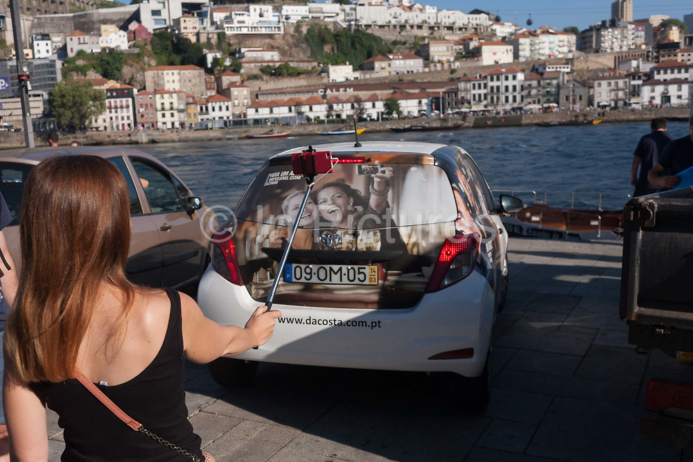 A young woman holds her selfie stick out at arms length to photograph herself with a background of the city behind, while in front of her is a car featuring a similar-looking lady doingthe same thing, on 20th July, in Porto, Portugal.