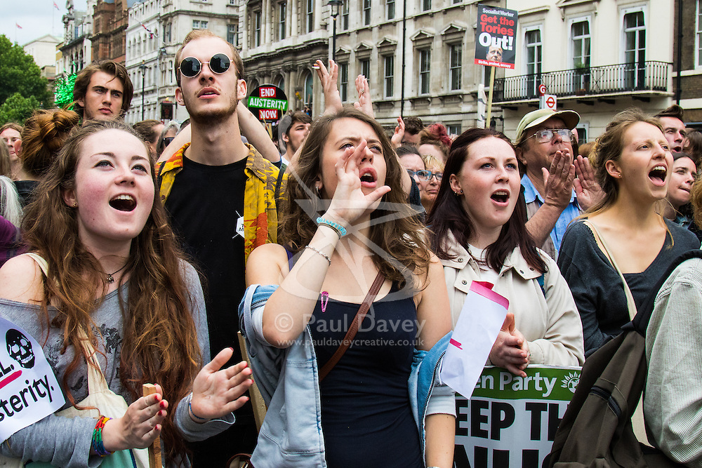 London, June 20th 2015. Thousands of people converge on the streets of London to join the People's Assembly Against Austerity's march from the Bank of England to Parliament Square. PICTURED: Protesters shout their derision at the Tory government whils watching speeches relayed to a big screen in Whitehall.