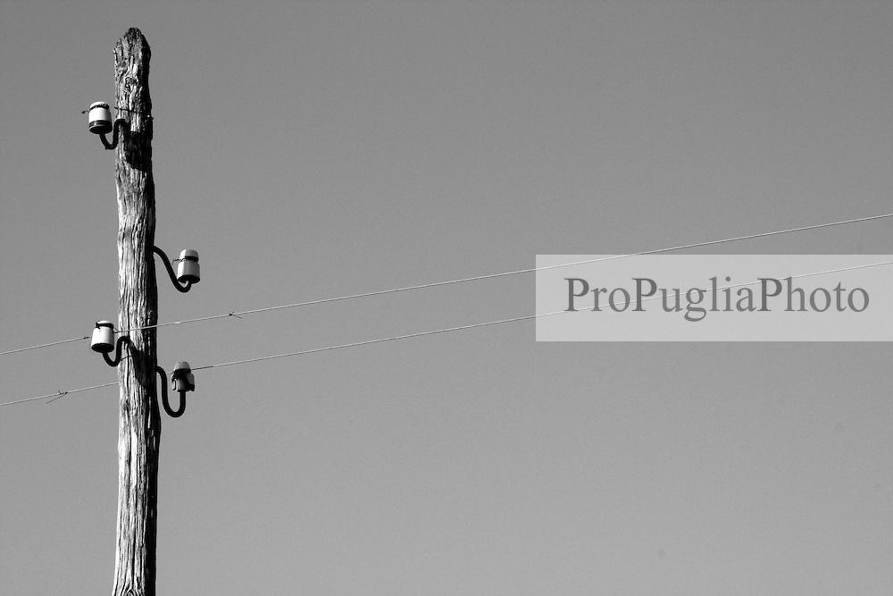 Reportage sul comune di Alessano per il progetto propugliaphoto..Vecchio palo elettrico in legno lungo i binari della ferroviaria sud est. .Macurano è un villaggio rupestre considerato un luogo di scambio e commercio, simbolo della cultura dell'olio per la presenza ad oggi di alcune tracce nelle grotte e di frantoi funzionanti nella zona. L'insediamento è caratterizzato da una serie di grotte sia naturali che scavate nel calcare, cisterne per la raccolta dell'acqua, sistemi di canalizzazione che scendono da Montesardo, viottoli, scalette e vie più larghe con antiche tracce di carri..Si ritiene che in questo sito, un vero e proprio centro abitato ben organizzato distante circa quattro km dalla costa, i monaci basiliani scappati dall'oriente in seguito alla lotta iconoclasta, trovarono rifugio e si dedicarono all'agricoltura..L'area del villaggio rupestre fu sicuramente sfruttata in epoche successive, lo prova l'esistenza di ben tre masserie di cui una fortificata e i resti di una serie di costruzioni che fanno parte dei numerosi esempi di architettura rurale presenti in questo territorio. .Il complesso masserizio, denominato Macurano, edificato probabilmente nel Cinquecento include la Masseria di Santa Lucia e la cappella di Santo Stefano. La Masseria è dominata dal nucleo originario, ovvero dalla torre cinquecentesca coronata da beccatelli a sostegno del parapetto aggettante del terrazzo sommitale.