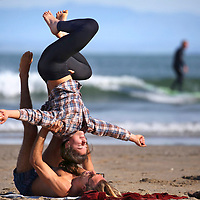 In a quintessentially Santa Cruz moment, and Shane Wright and yoga instructor Delaney Puhek practice Acro-Yoga during low tide at Cowell Beach in Santa Cruz while a surfer catches a ride at Indicators surf break behind them. Acroyoga has its roots in the beginning of the 20th century and has been developed by practitioners since then, and the practice has a number of different styles. Practioners mix more classic yoga poses with dance, Thai massage and calisthenics. Acro in Greek  means high, or elevated and Yoga in Sanskrit commonly translates to notions of union, or joining.<br /> Photo by Shmuel Thaler <br /> shmuel_thaler@yahoo.com www.shmuelthaler.com