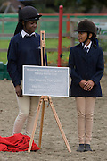 Two young girl horse riders stand by a plaque just unveiled by Queen Elizabeth while making a brief visit to the Ebony Horse Club at Loughborough Junction, Brixton, London. Accompanied by the Duchess of Cornwall, Her Majesty watched an equestrian demonstration in one of the most disadvantaged inner city neighbourhoods in the country where there is a historic legacy of under-achievement in schools, high rates of teenage pregnancy and negative stereotypes of young people, gang violence and drug related crime.