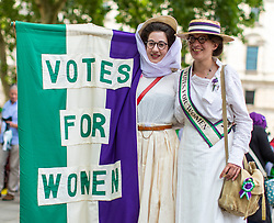 © Licensed to London News Pictures. 10/06/2018. London, UK. Two women dressed as Suffragettes stand with a 'Votes for Women' banner in Parliament Square after thousands of people marched through central London wearing green, white and violet, the colours of the Suffragette movement,  to celebrate 100 years votes for women. Photo credit: Rob Pinney/LNP
