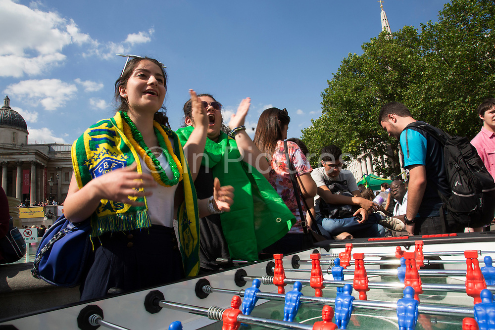 London, UK. Thursday 12th June 2014. Playing table football. Brazilians gather for the Brazil Day celebrations in Trafalgar Sq. A gathering to celebrate the beginning of the Brazil 2014 FIFA World Cup. Revellers sing and dance and play football games and all in the yellow green and blue of the Brazilian flag.