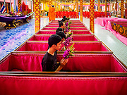 "29 MARCH 2017 - BANG KRUAI, NONTHABURI, THAILAND: People sit in their coffins during their ritualistic rebirth during a ""Resurrection Ceremony"" at Wat Ta Kien (also spelled Wat Tahkian), a Buddhist temple in the suburbs of Bangkok. People go to the temple to participate in a ""Resurrection Ceremony."" Groups of people meet and pray with the temple's Buddhist monks. Then they lie in coffins, the monks pull a pink sheet over them, symbolizing their ritualistic death. The sheet is then pulled back, and people sit up in the coffin, symbolizing their ritualist rebirth. The ceremony is supposed to expunge bad karma and bad luck from a person's life and also get people used to the idea of the inevitability of death. Most times, one person lays in one coffin, but there is family sized coffin that can accommodate up to six people. The temple has been doing the resurrection ceremonies for about nine years.          PHOTO BY JACK KURTZ"