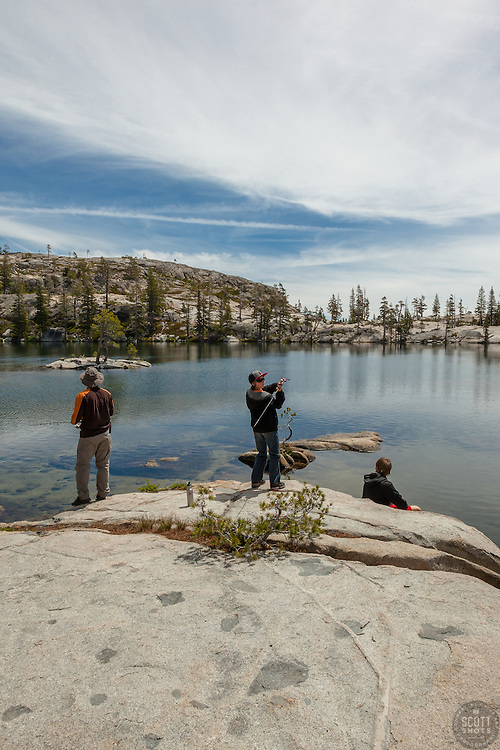 """""""Fishing Paradise Lake"""" - Photograph of a man and two boys fishing from a boulder at Paradise Lake in the Tahoe National Forest."""