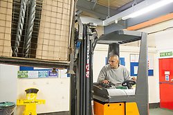 A prisoner working in a workshop driving a forklift, prison
