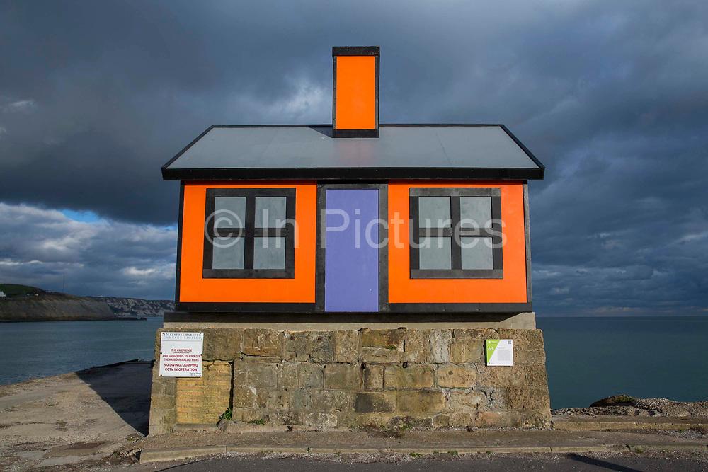 An orange bungalow on the edge of Folkestone harbour built by the artist Richard Woods as part of the 2017 Folkestone Triennial. Folkestone, Kent. The artist wanted to create a piece about the housing crisis in the UK.