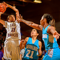 Kirtland Central Bronco Deiondra Smith (11), left, shoots above Cleveland Storm Alyssa Lucero (21) and Jade Hill (10) during the John Lomasney Invitational basketball tournament at Gallup High School Friday.