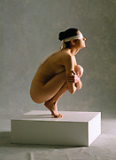 Blindfolded nude woman crouching on a white platform
