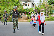 """Sept. 27, 2009 -- PATTANI, THAILAND: Thai soldiers provide security for children walking to the Gahong School in Pattani, Thailand, Sept 27. Schools and school teachers have been frequent targets of Muslim insurgents in southern Thailand and the army now provides security at many government schools.  Thailand's three southern most provinces; Yala, Pattani and Narathiwat are often called """"restive"""" and a decades long Muslim insurgency has gained traction recently. Nearly 4,000 people have been killed since 2004. The three southern provinces are under emergency control and there are more than 60,000 Thai military, police and paramilitary militia forces trying to keep the peace battling insurgents who favor car bombs and assassination.  Photo by Jack Kurtz / ZUMA Press"""