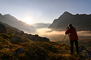 Photographer with the view towards the Engadin from the mountain pass Julier in the morning, Parc Ela, Grisons, Switzerland