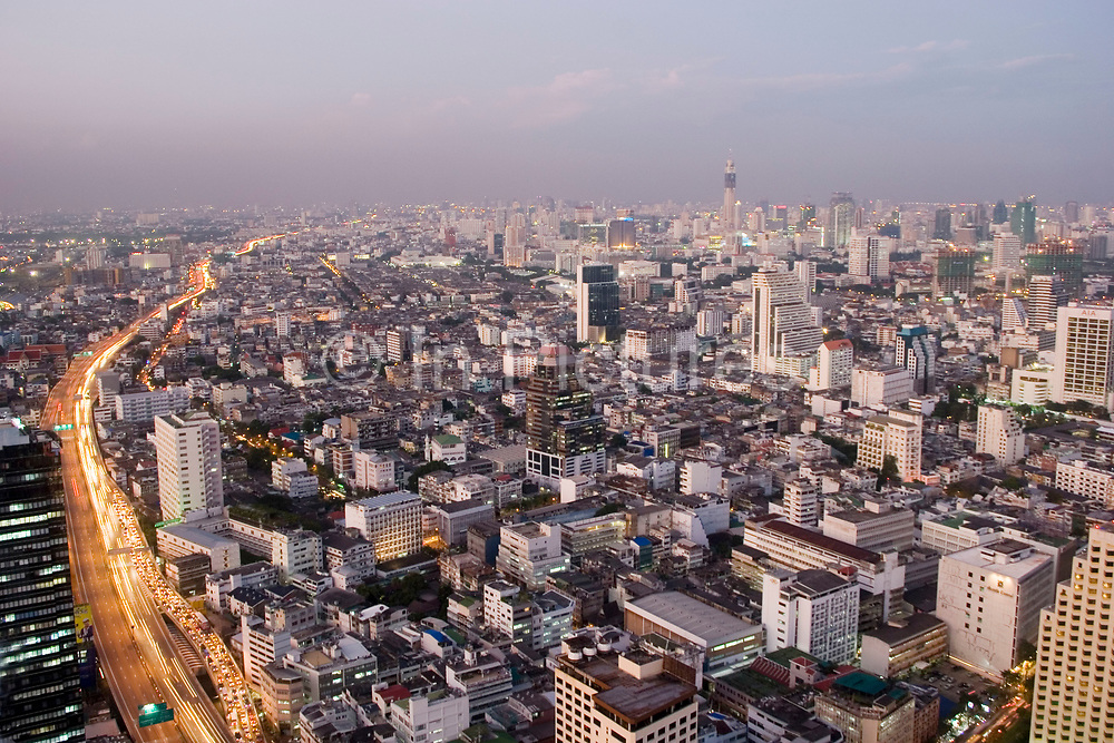 Bangkok skyline viewed from the 54th floor of the Lebua Hotel at State Tower in Silom district at sundown. Cars run through the city on the expressways below, and Bangkok's status as an highrise giant of Asia is unquestionable.