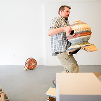 041015  Adron Gardner/Independent<br /> <br /> University of New Mexico art teacher John Zimmerman carries a piece of his art to a display pedestal at Art123 in Gallup Friday.