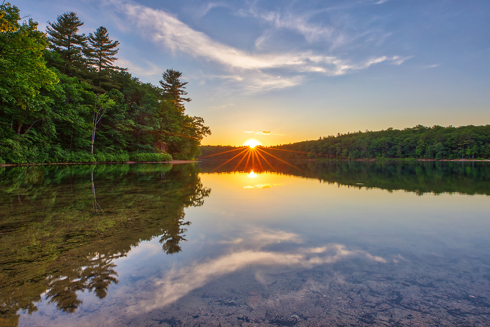 Sunset reflection at Walden Pond in Concord showing a magical mixture of trees and orange hues. I was on my way to the Minute Man National Historic Park when I realized that there might be spectacular sunset light to be photographed. I quickly pulled over, made my way to the banks of this famous pond that Thoreau ones called home, and took a few photographs. <br /> <br /> Walden Pond sunset photography images are available as museum quality photography prints, canvas prints, acrylic prints or metal prints. Prints may be framed and matted to the individual liking and room decor needs:<br /> <br /> https://juergen-roth.pixels.com/featured/scenic-massachusetts-walden-pond-juergen-roth.html<br /> <br /> Good light and happy photo making!<br /> <br /> My best,<br /> <br /> Juergen