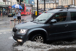 © Licensed to London News Pictures. 25/07/2021. London, UK. A car drives through a section of flooded road in Greenwich Town Centre in South East London . An amber weather warning for thunderstorms is in place in parts of London and the South East . Photo credit: George Cracknell Wright/LNP