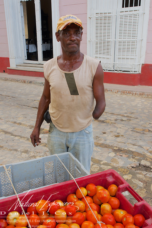 A local man selling tomatoes on the streets of Trinidad, Cuba.