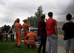 © Licensed to London News Pictures. 01/09/2013. Leyland, UK people watch as fire crews put out the fire. The scene at Leyland St Mary's Catholic Technology College in Leyland, Lancashire as it was devastated by the blaze at 4pm yesterday (1st September 2013), which saw 100ft flames - and was tackled by 125 firefighters and 20 engines. Photo credit : Pat Tack/LNP