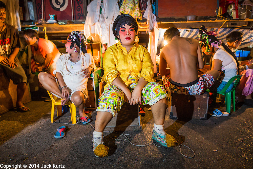 """19 AUGUST 2014 - BANGKOK, THAILAND:  Members of the cast of the Lehigh Leng Kaitoung Opera troupe relax backstage before a performance near the Chaomae Thapthim Shrine, a small Chinese shrine in a working class neighborhood of Bangkok. The performance was for Ghost Month. Chinese opera was once very popular in Thailand, where it is called """"Ngiew."""" It is usually performed in the Teochew language. Millions of Chinese emigrated to Thailand (then Siam) in the 18th and 19th centuries and brought their culture with them. Recently the popularity of ngiew has faded as people turn to performances of opera on DVD or movies. There are still as many 30 Chinese opera troupes left in Bangkok and its environs. They are especially busy during Chinese New Year and Chinese holiday when they travel from Chinese temple to Chinese temple performing on stages they put up in streets near the temple, sometimes sleeping on hammocks they sling under their stage. Most of the Chinese operas from Bangkok travel to Malaysia for Ghost Month, leaving just a few to perform in Bangkok.        PHOTO BY JACK KURTZ"""