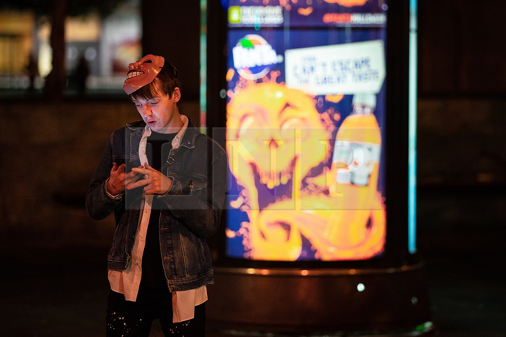 © Licensed to London News Pictures . 28/10/2018. Manchester, UK. A man uses his mobile phone in Piccadilly Gardens . Revellers on a night out , many in fancy dress , on the weekend before Halloween . Photo credit: Joel Goodman/LNP