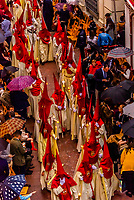 Hooded Penitents (Nazarenos) in the procession of the Brotherhood (Hermandad) La Lanzada, Holy Week (Semana Santa), Seville, Andalusia, Spain.