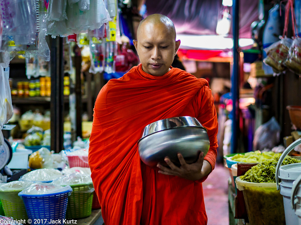 08 JUNE 2017 - BANGKOK, THAILAND: A Buddhist monk makes his alms round in Khlong Toey Market, Bangkok's main fresh market. Thai consumer confidence dropped for the first time in six months in May following a pair of bombings in Bangkok, low commodity prices paid to farmers and a sharp rise in the value of the Thai Baht versus the US Dollar and the EU Euro. The Baht is surging because of political uncertainty, related to Donald Trump, in the US and Europe. The Baht's rise is being blamed for a drop in Thai exports. This week the Baht has been trading at around 33.90 Baht to $1US, it's highest point in two years.      PHOTO BY JACK KURTZ