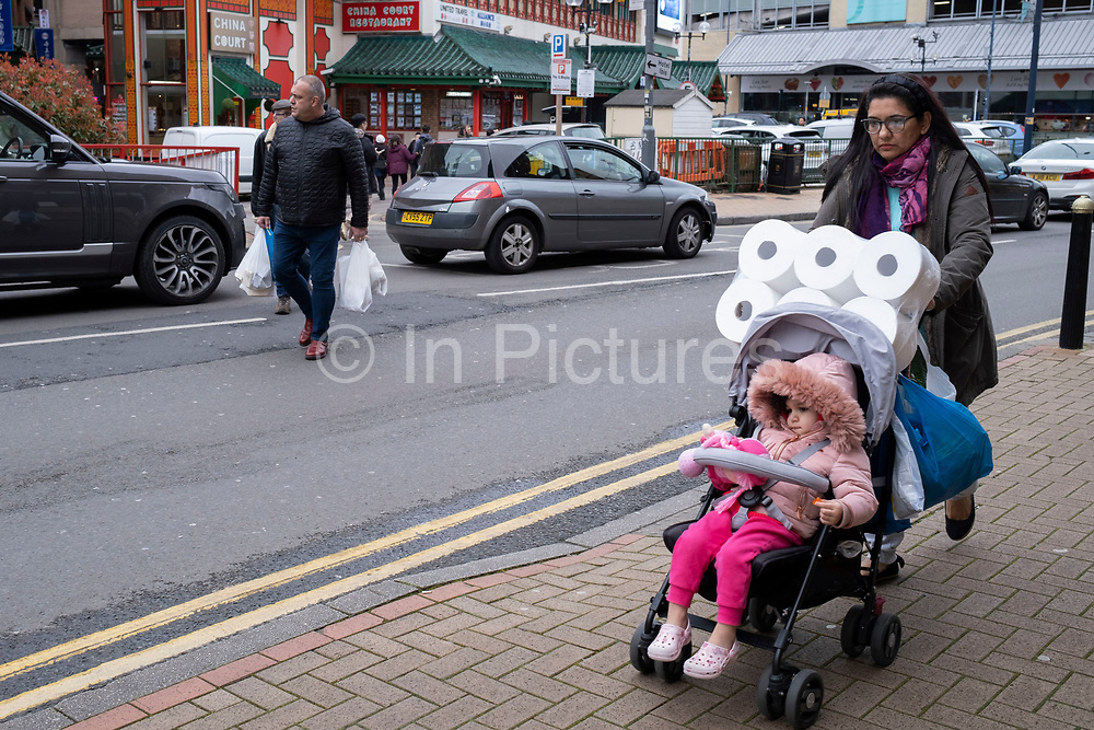 Woman buying large toilet rolls on 14th March 2020 in Birmingham, United Kingdom. Following the Coronavirus outbreak, many people have started to bulk buy or panic buy larger numbers of toilet rolls, or other similar paper products.