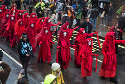 London, UK. 12 October, 2019. The Red Brigade leads thousands of climate activists from Extinction Rebellion taking part in the XR March from Marble Arch to Russell Square on the sixth day of International Rebellion protests to demand a government declaration of a climate and ecological emergency, a commitment to halting biodiversity loss and net zero carbon emissions by 2025 and for the government to create and be led by the decisions of a Citizens' Assembly on climate and ecological justice. Credit: Mark Kerrison/Alamy Live News