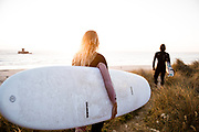 Couple holding surfboards, staring out at the sea at La Rocco Tower, St Ouen's Bay, Jersey, CI ready to go surfing in the golden sunlight.