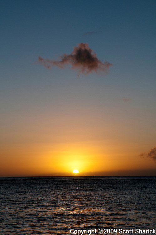 The sun sets in Hawaii with a single cloud in the sky.