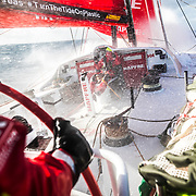 Leg 7 from Auckland to Itajai, day 11 on board MAPFRE, surfing the southern ocean, Sophie Ciszek at the hatch protecting herself from the waves, 28 March, 2018.