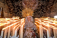 """The structure of the paso, the float carrying the Virgin, is carved and decorated with fabric, flowers and several rows of candles that are continuously kept alight.  The """"dolorosas"""" are covered by an ornate canopy or baldachin (palio) attached to the structure. Seville, Spain"""