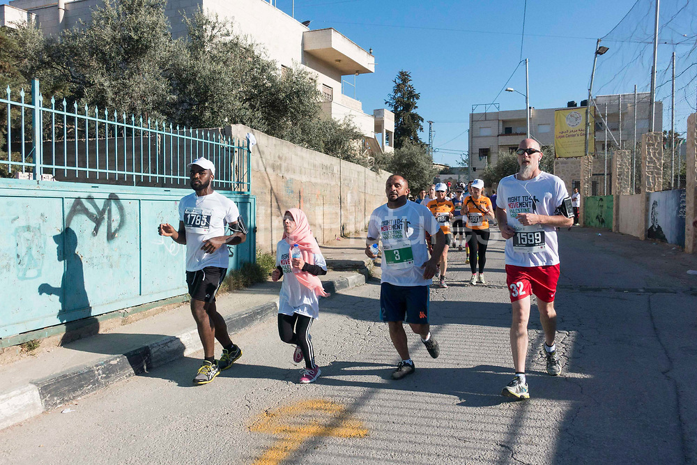 Participants running through the AlAzza refugee camp during the Palestine Marathon on 1st April 2016 in Bethlehem, West Bank. During the Palestine Marathon, thousands of runners, both professional and amateur come from across the globe to take part in the Right to Movement event.