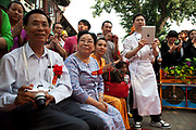 Audience watching traditional dancers dressed in beautiful costumes perform a dance on a day of cultural celebration in Shichahai area, near to Yandai Xiejie. Shichahai dates back to the Jin Dynasty. Around the lake there are ten famous Taoist and Buddhist temples and several formal royal mansions and gardens. The borders of the lakes are surrounded by large trees making Shichahai a famous scenic spot. In 1992 the municipal government of Beijing declared the district a Historical and Cultural Scenic District.
