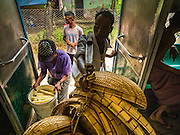 26 OCTOBER 2015 - YANGON, MYANMAR:  A basket vendor gets on the Yangon Circular Train at the Pa Ywet Kone Station. The Yangon Circular Railway is the local commuter rail network that serves the Yangon metropolitan area. Operated by Myanmar Railways, the 45.9-kilometre (28.5mi) 39-station loop system connects satellite towns and suburban areas to the city. The railway has about 200 coaches, runs 20 times daily and sells 100,000 to 150,000 tickets daily. The loop, which takes about three hours to complete, is a popular for tourists to see a cross section of life in Yangon. The trains run from 3:45 am to 10:15 pm daily. The cost of a ticket for a distance of 15 miles is ten kyats (~nine US cents), and for over 15 miles is twenty kyats (~18 US cents).    PHOTO BY JACK KURTZ