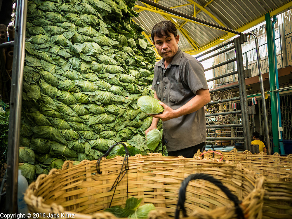 """11 AUGUST 2016 - BANGKOK, THAILAND:  A worker unloads a truck of cabbage in the produce section of Pak Khlong Talat in Bangkok. Pak Khlong Talat (literally """"the market at the mouth of the canal"""") is the best known flower market in Thailand. It is the largest flower market in Bangkok. Most of the shop owners in the market sell wholesale to florist shops in Bangkok or to vendors who sell flower garlands, lotus buds and other floral supplies at the entrances to temples throughout Bangkok. There is also a fruit and produce market which specializes in fresh vegetables and fruit on the site. It is one of Bangkok's busiest markets and has become a popular tourist attraction.         PHOTO BY JACK KURTZ"""